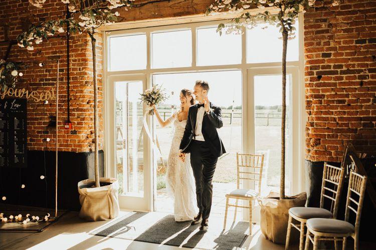 Bride and Groom Entering the Rustic Barn Wedding Reception