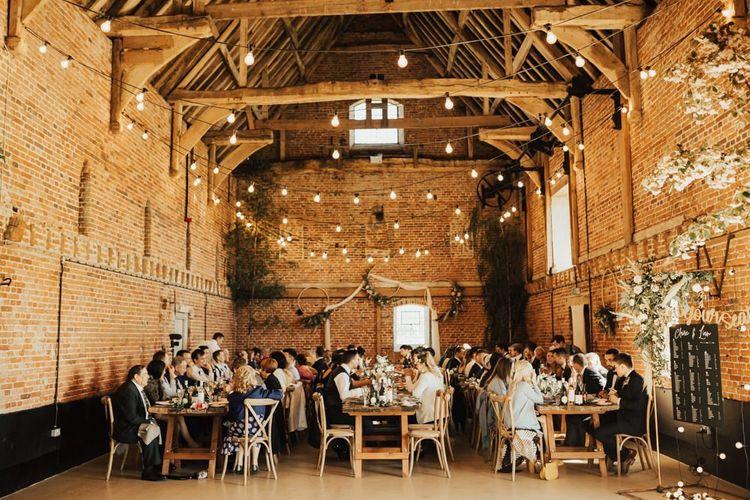 Godwick Barn Wedding Reception with Wooden Tables, Festoon Lights and Foliage Decor