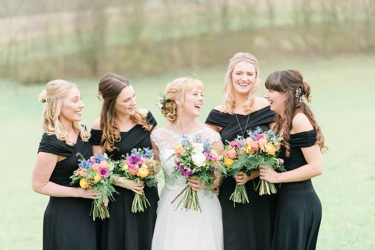 Black bridesmaid dresses with bright wildflower bouquets