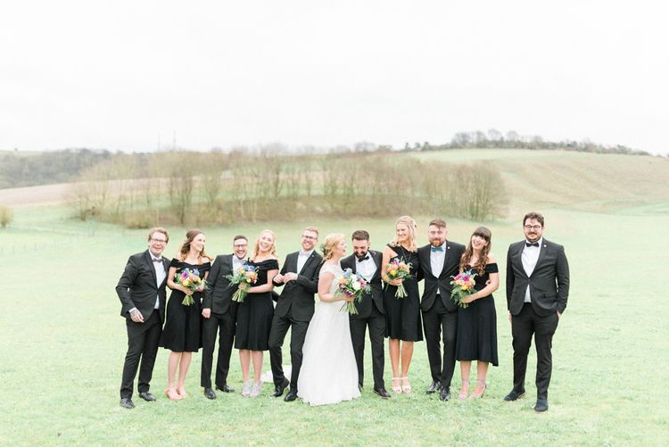 Black bridesmaid dresses with groomsmen in tuxedos