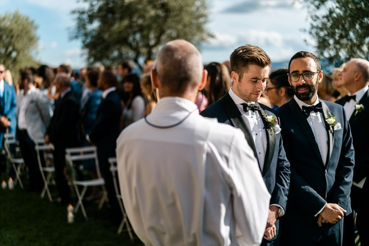 Outdoor WEdding Ceremony | Groom at the Altar in Navy Tuxedo | Luxe Pink & White Destination Wedding at La Bastide de Gordes in Provence, France, Styled by Haute Wedding | John Barwood Photography | Motion Craft Creative