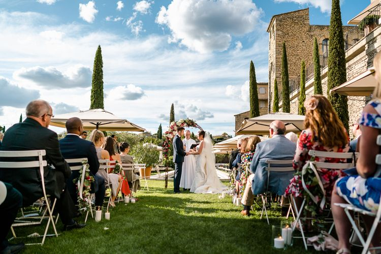 Outdoor Wedding Ceremony | Bride in  Carolina Herrera Gown | Groom in Navy Edit Suits Tuxedo | Luxe Pink & White Destination Wedding at La Bastide de Gordes in Provence, France, Styled by Haute Wedding | John Barwood Photography | Motion Craft Creative