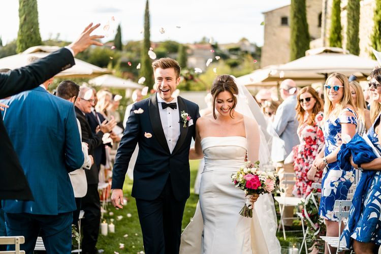 Outdoor Wedding Ceremony | Confetti Exit | Bride in  Carolina Herrera Gown | Groom in Navy Edit Suits Tuxedo | Luxe Pink & White Destination Wedding at La Bastide de Gordes in Provence, France, Styled by Haute Wedding | John Barwood Photography | Motion Craft Creative