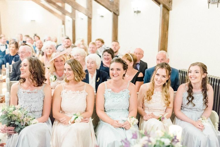 Wedding Ceremony with Bridesmaids Sitting in Pastel Coast Dresses