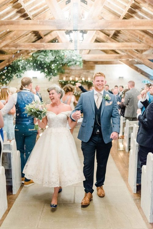 Bride in Tea Length Wedding Dress and Groom in Blue Moss Bros. Suit Walking Up the Aisle as Husband and Wife
