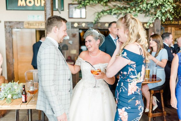 Bride in Tea Length Wedding Dress with Short Hair and Birdcage Veil Talking to Wedding Guests