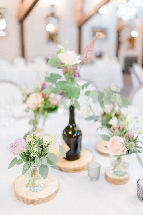 Wedding Reception Table Centrepiece of Pink Flower Stems in Jars on Wood Tree Slice