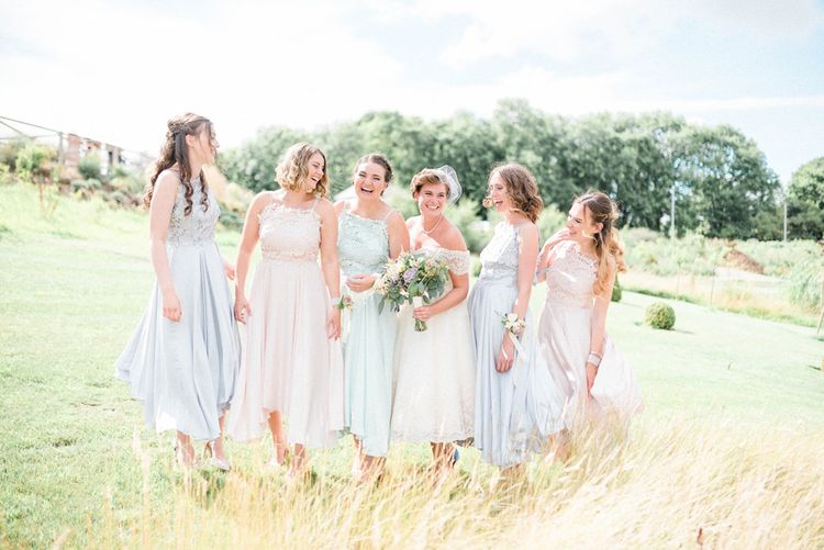 Bridal Party Portrait with Bridesmaids in Pastel Blue and Pink Coast Dresses and Bride in Tea Length Wedding Dress