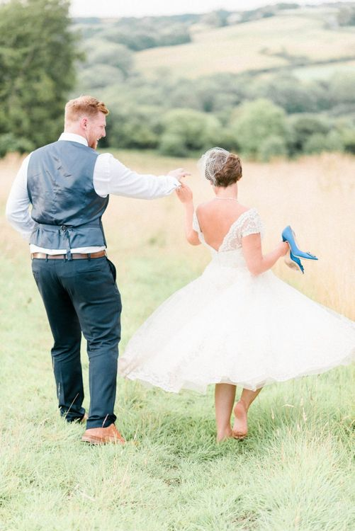 Bride in Tea Length Wedding Dress, Birdcage Veil and Blue Manolo Blahnik Hangisi Shoes and Groom in Moss Bros. Suit Dancing in the Fields