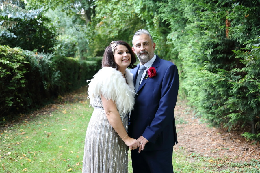 sparkly wedding dress, feather shrug, blue suit. quirky wedding at manuden church, essex