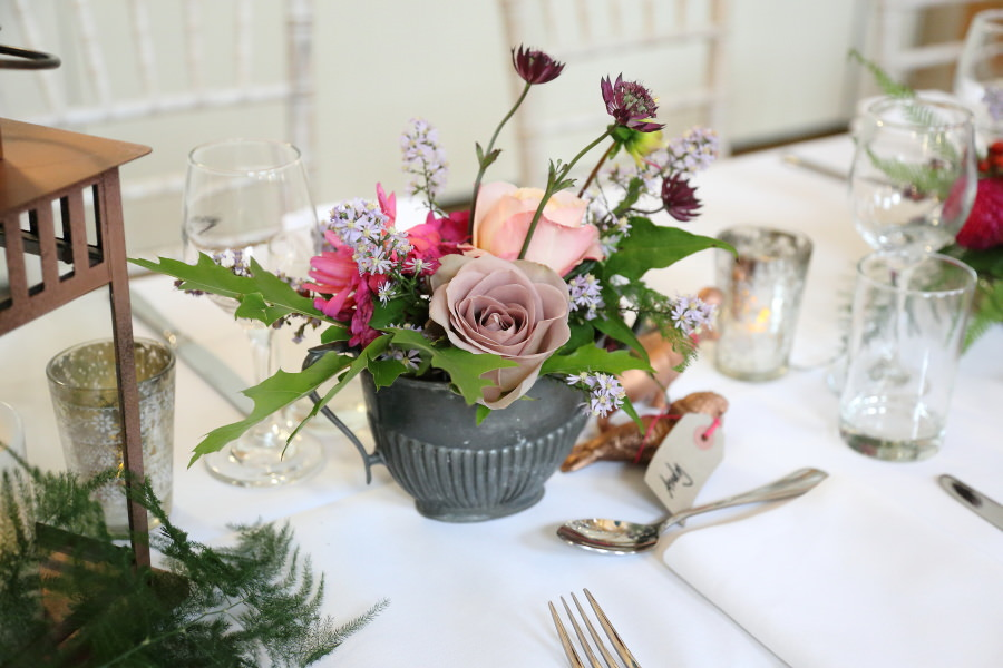 pretty flowers in quirky vases at manuden village hall wedding