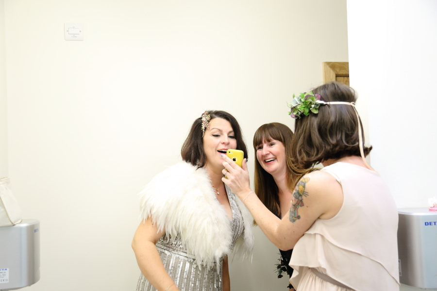 alternative quirky wedding photography, bride and friends looking at phone in the loos