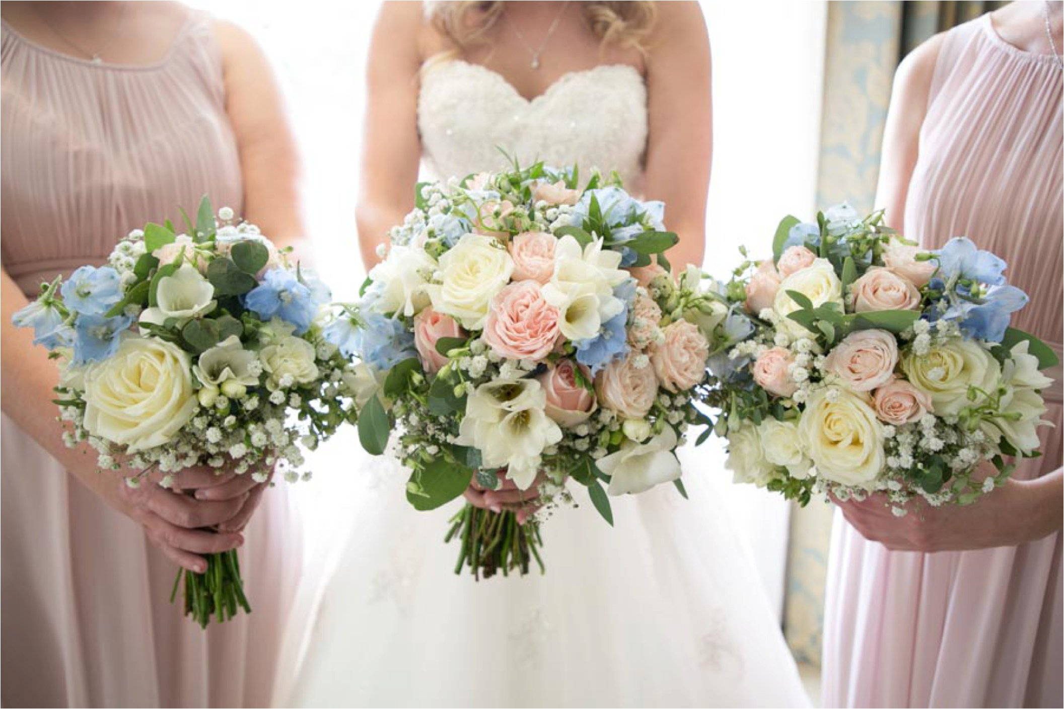bride and bridesmaids holding up pastel flowers