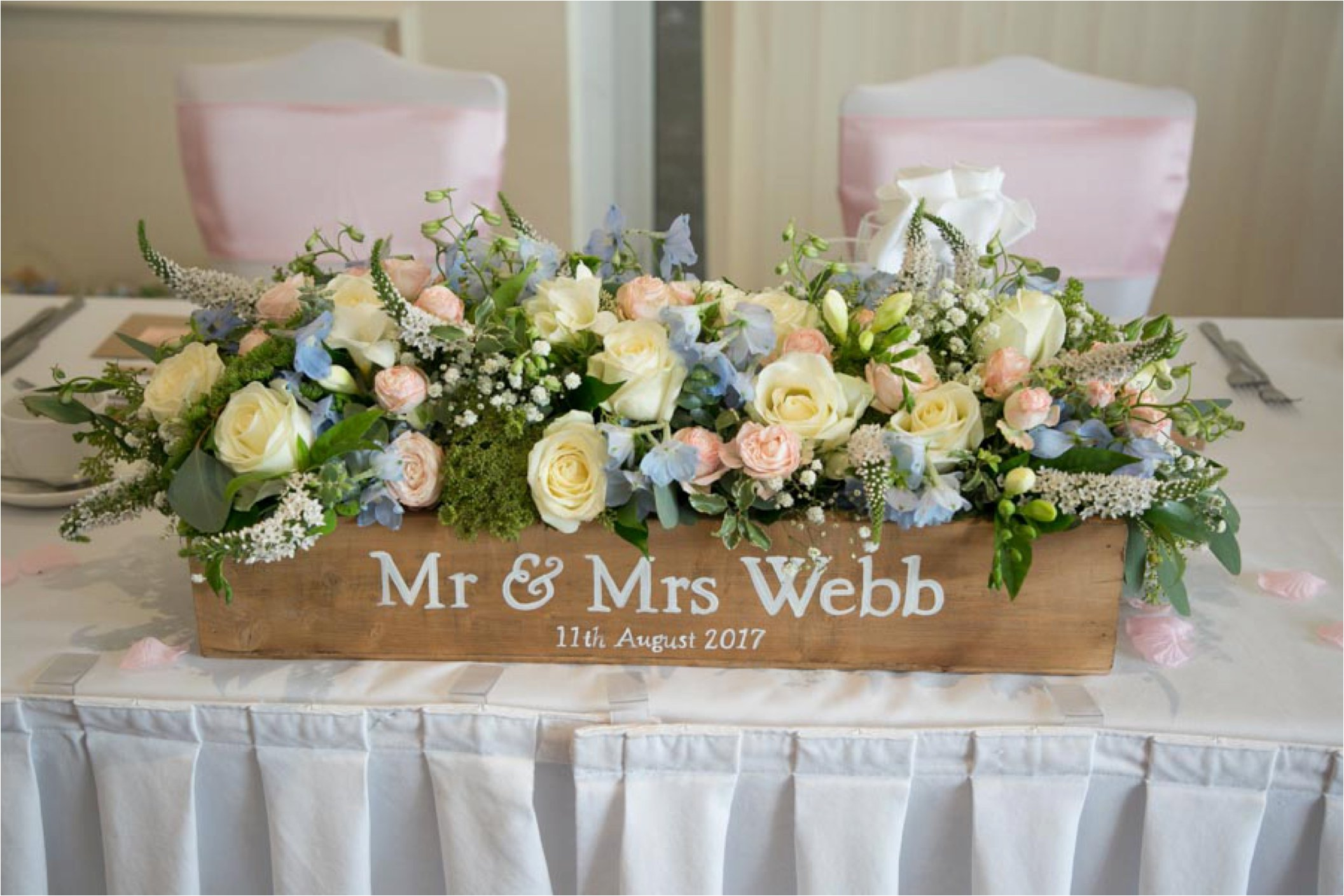 flowers in wooden box at wedding on top table