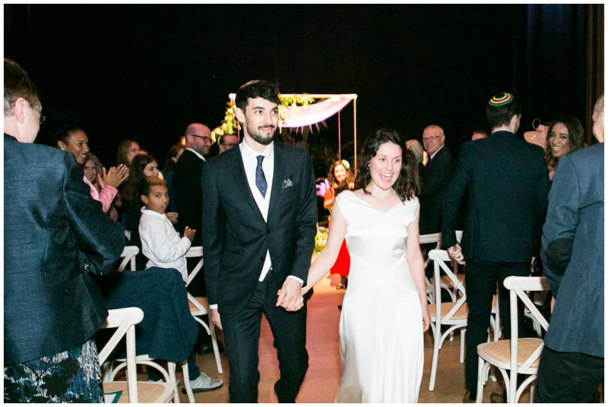 bride and groom looking happy walking down isle after jewish wedding