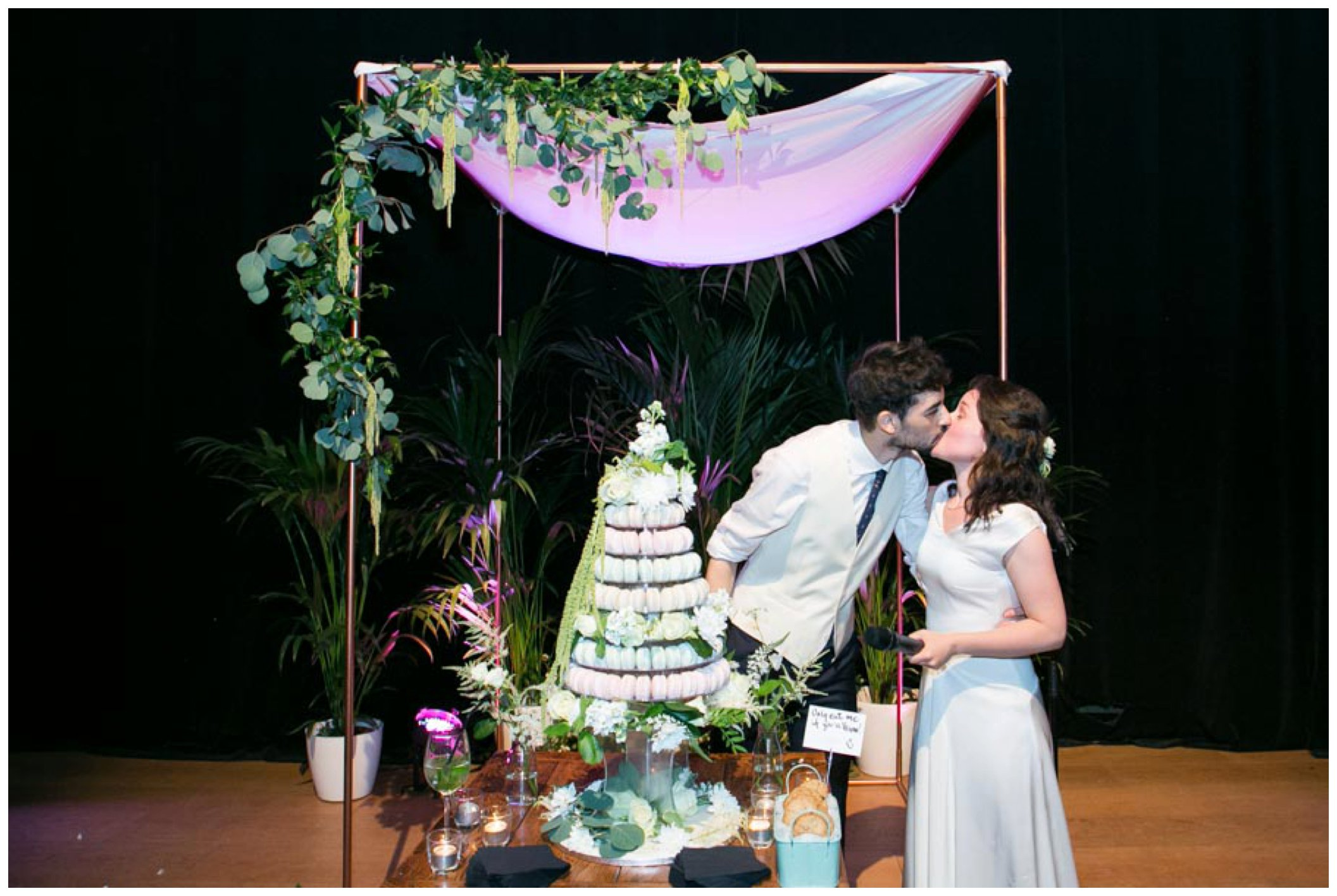 bride and groom kiss infront of macaroon tower