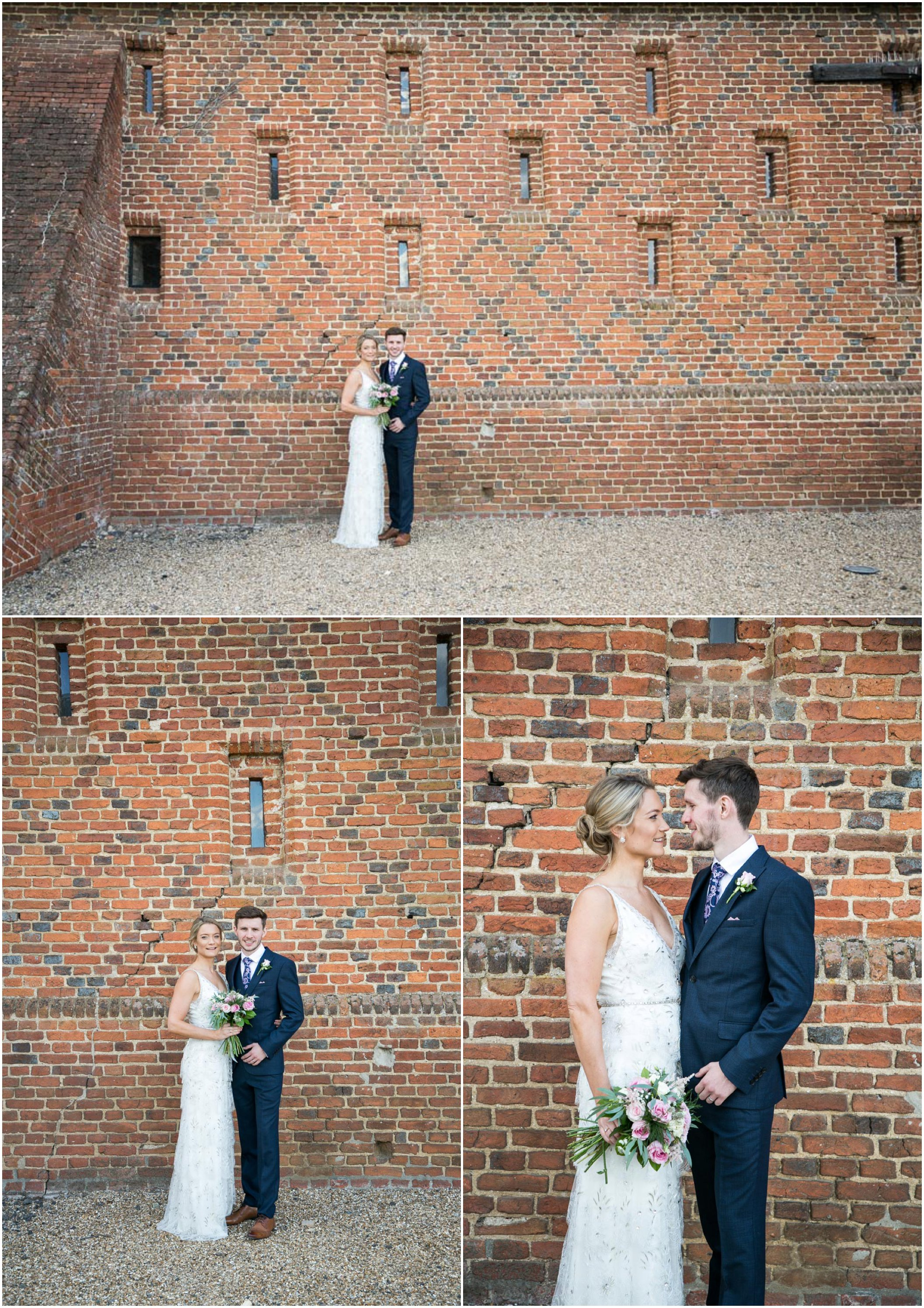 bride in jenny packham long dress and groom in navy suit, naturally posing infront of barn wall infront