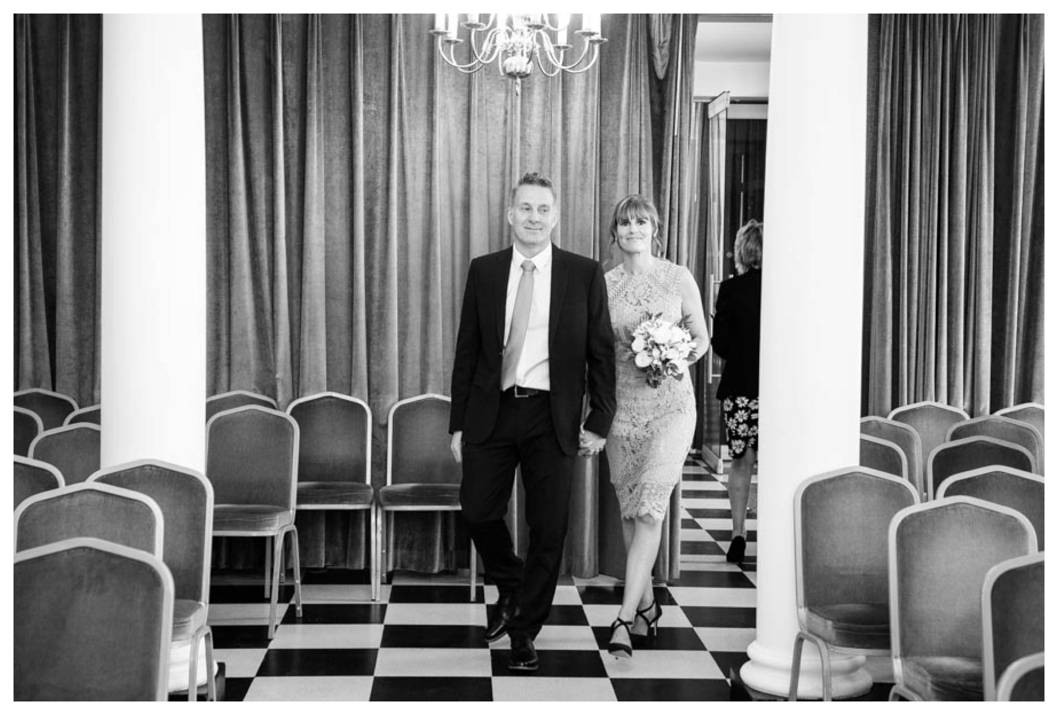black and white photo bride and groom walking into register office together