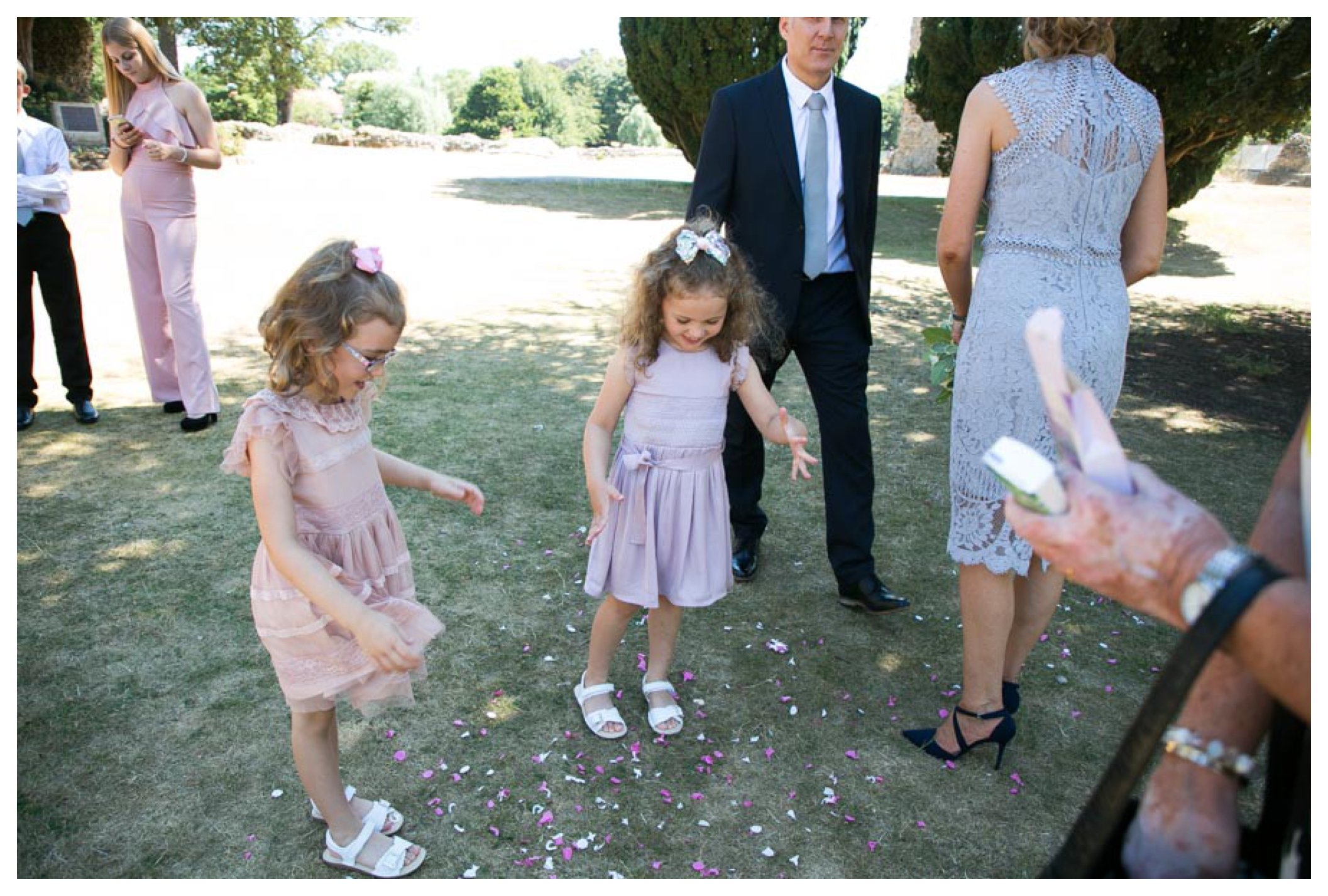 two girls in flower girl dresss playing with confettii at summer wedding