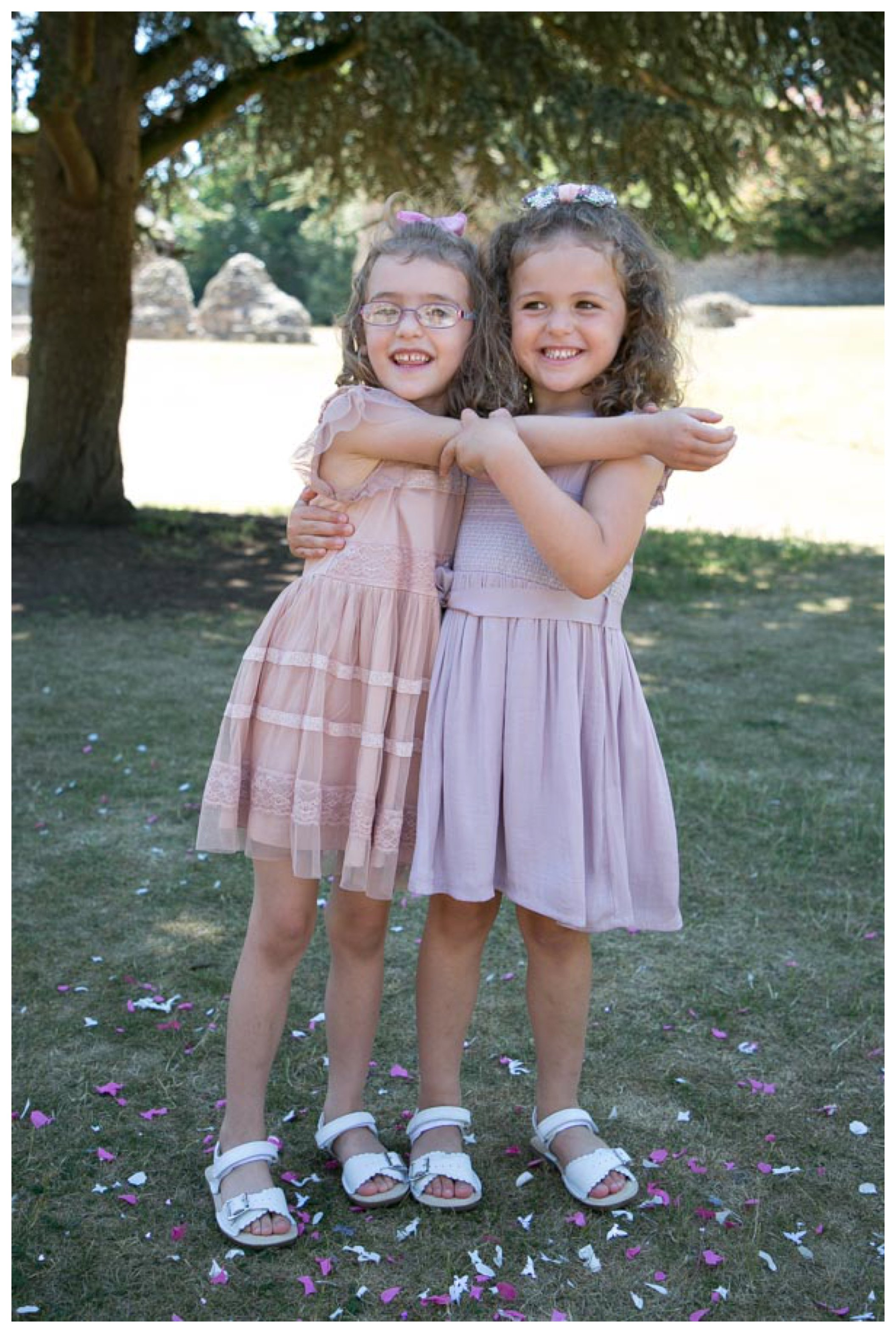 twin girls in flower girl pastel coloured dresses at parents wedding