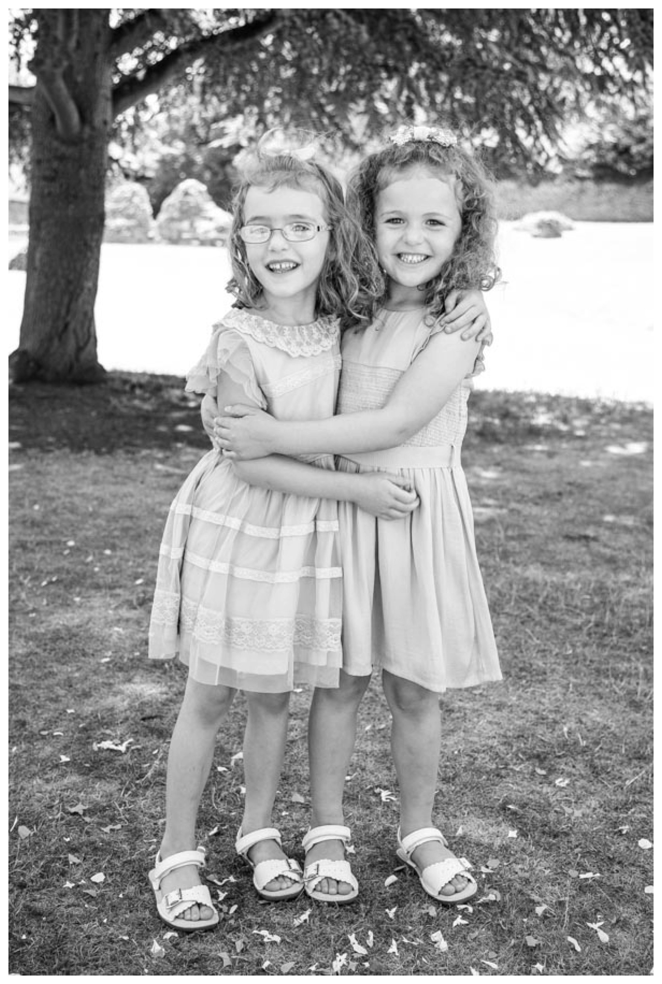 twin girls black and white photo standing in confettii