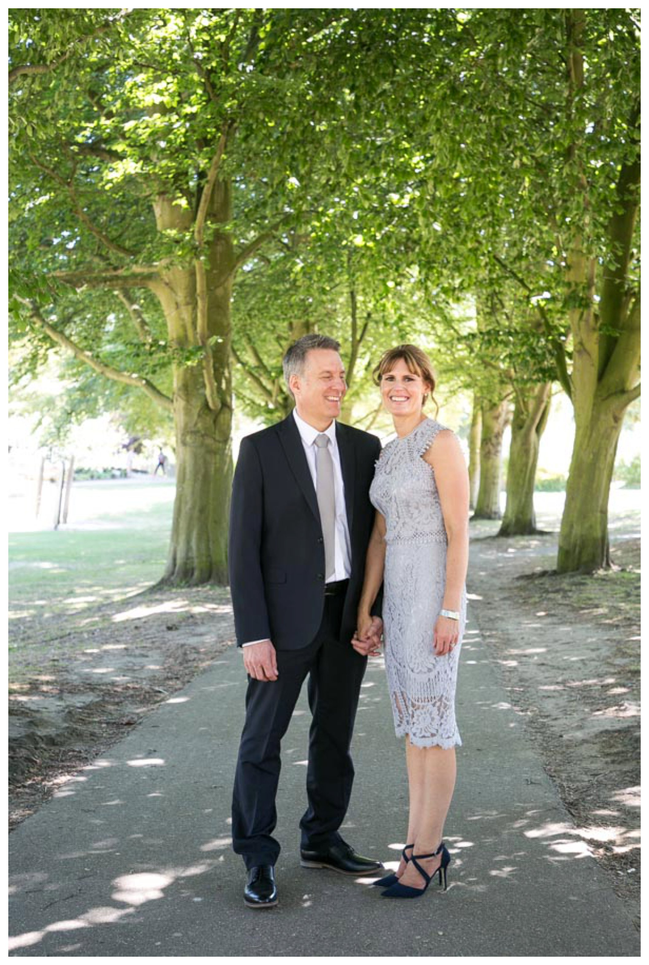 just married couple smiling on pathway with large trees behind