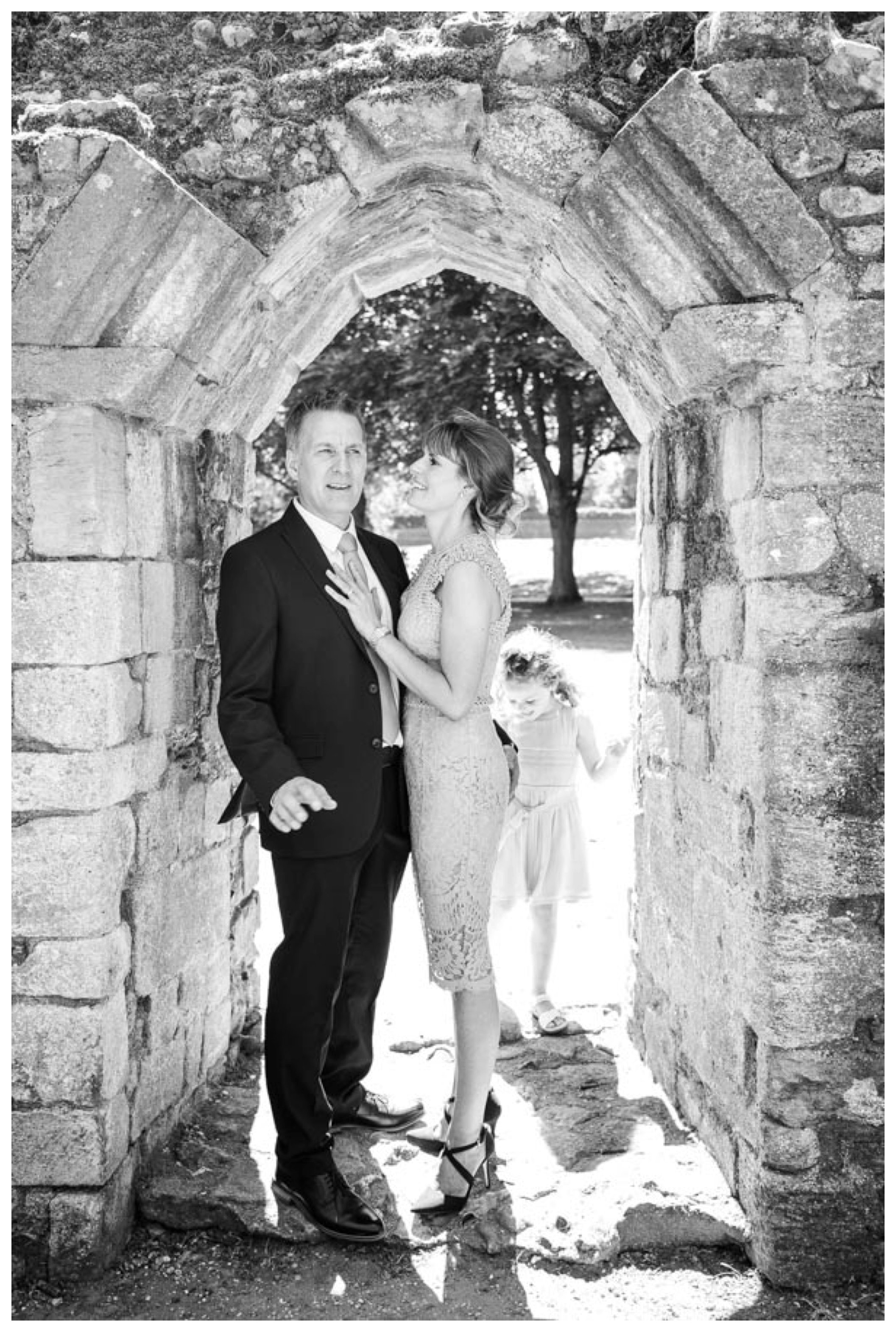 archway at abbey gardens, bury st edmunds with just married couple and daughter