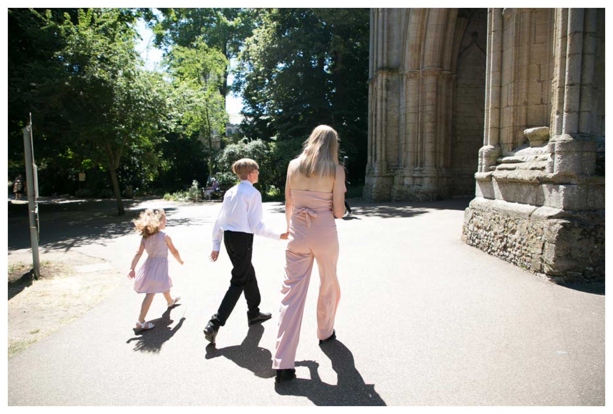 three children walking together towards large archway