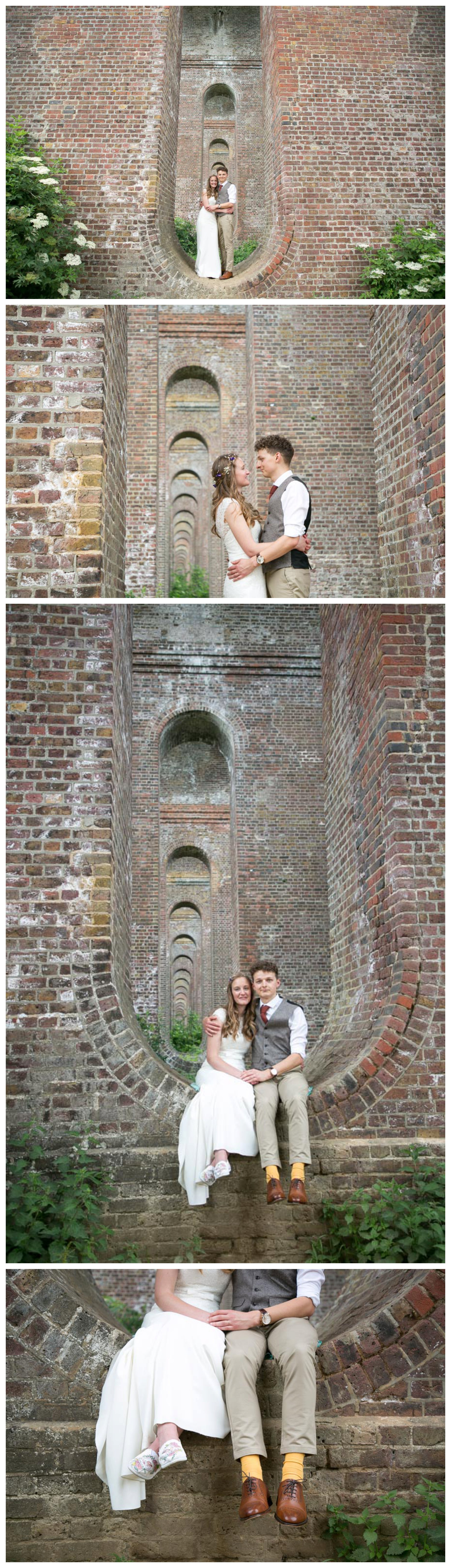 bride and groom portriats at Chappel viaduct, sitting in viaduct curve, bridge going off into distance
