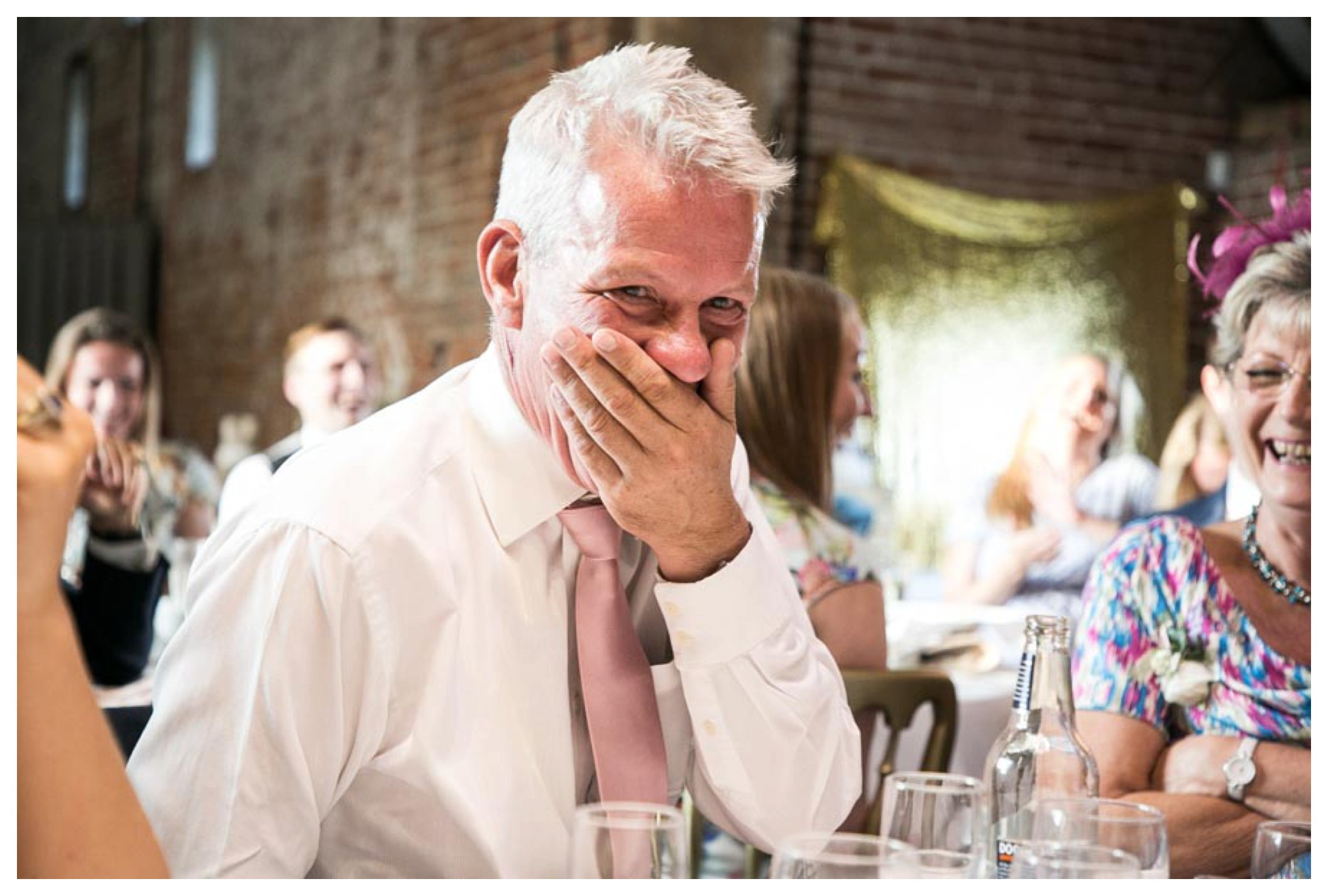 father of groom with hand over his mouth looking shocked at grooms speech