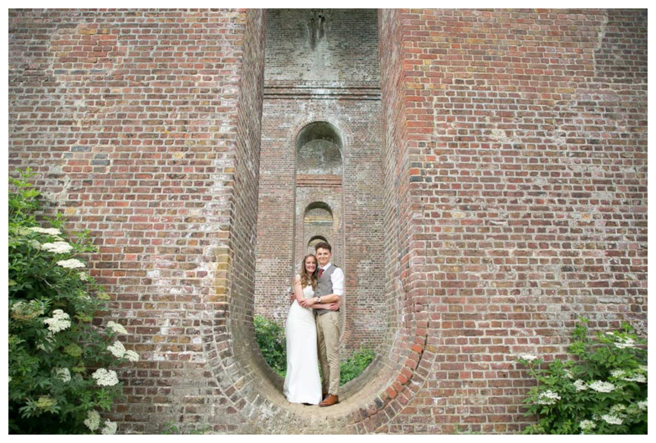 bride and groom wedding portriat photograph as they stand in a viaduct in essex