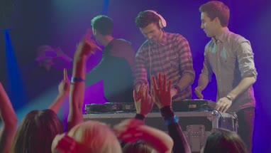 Man operating DJ machine and his friends dancing on music in nightclub