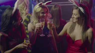 Female friends having fun with champagne and talking in nightclub