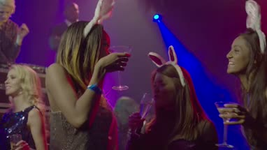 Female friends dancing and having fun with champagne in nightclub