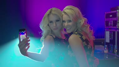 Female friends taking self photograph with mobile phone in nightclub