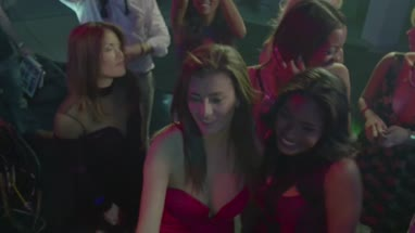 Friends taking self photograph with mobile phone while enjoying music in nightclub
