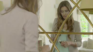 Woman looking into mirror and applying perfume