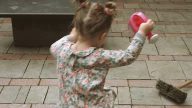 Baby girl holding toy watering can and running outside home