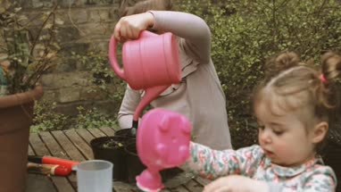 Girls holding plastic watering can and watering plant in backyards