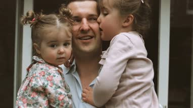 Father holding two daughters and they kissing on his cheek