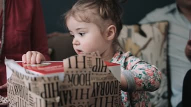 Cute little girl unwrapping gift box