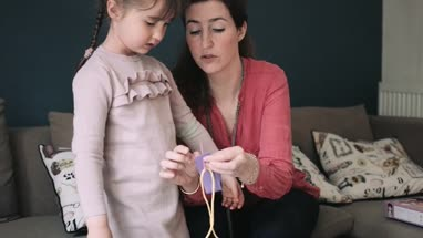 Mother helping daughter to do craft work in living room