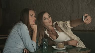 Female friends sitting and holding mobile phone while taking selfie in coffee bar
