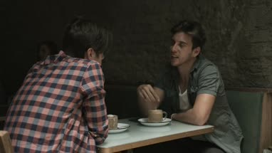 Male friends sitting and talking in coffee bar