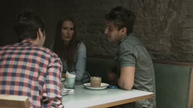 Friends laughing and talking while sitting in coffee bar