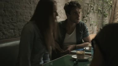 Male and female friends talking while sitting in coffee bar