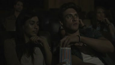 Friends watching cinema and eating popcorn in Movie Theatre