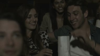 Woman giving popcorn box to friends while they enjoying cinema in Movie Theatre