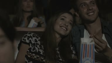 Friends enjoying cinema and eating popcorn in Movie Theatre