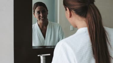 Woman wears bathrobe looking into mirror and washing hands in bathroom